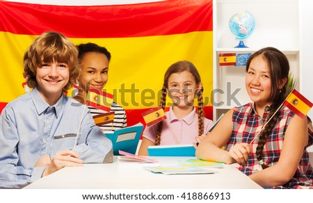 Four happy multiethnic students holding flags