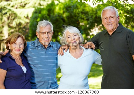Four happy semiling senior people standing in nature in summer - stock photo