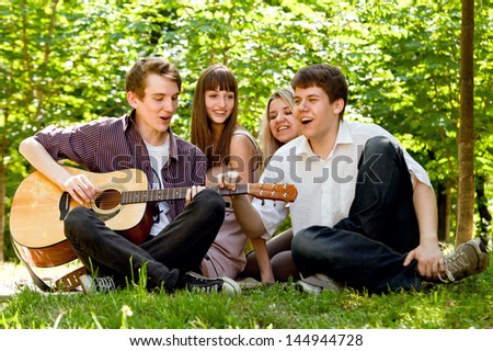 Four happy smiling teenage friends singing by guitar - stock photo