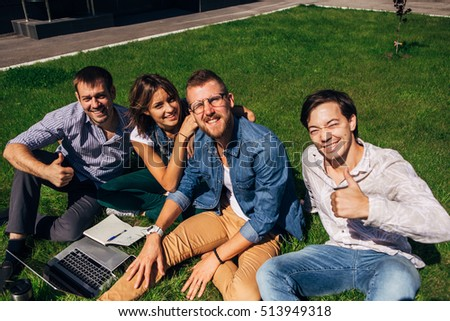 Four happy students sitting on lawn