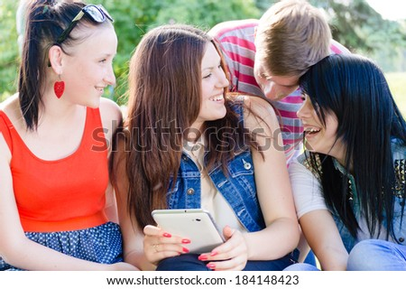 Four happy teen friends having fun laughing on selfie or selfy picture of themselves on summer outdoors background portrait