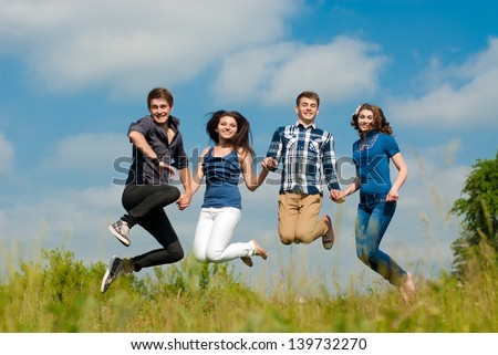 Four happy teenage friends boys and girls jumping high in blue sky