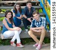 Four happy teenage friends boys and girls sitting on stairs outdoor - stock photo