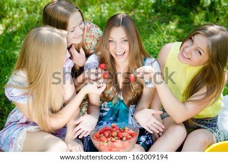Four happy teenage girls eating strawberry and having fun outdoors on summer day - stock photo
