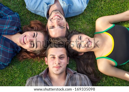Four happy teenagers lying head to head on their backs on the green grass smiling up at the camera