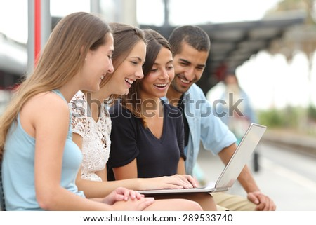 Four happy tourist friends sharing a laptop sitting in a train station while they are waiting - stock photo