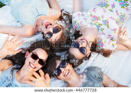 Four happy women wearing trendy sunglasses - stock photo
