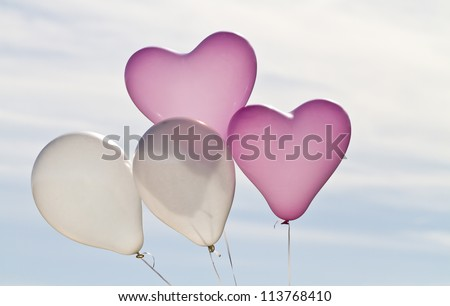 Four helium filled balloons against the sky, two pink and heart shaped the others white