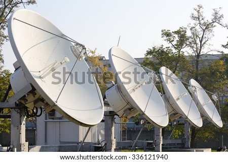 Four high power satellite antennae facing the sky.