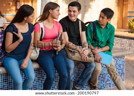 Four high school friends with backpacks and books hanging out after school