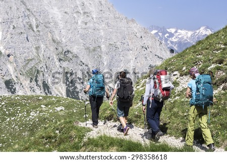 Four hikers on a way to the top - stock photo