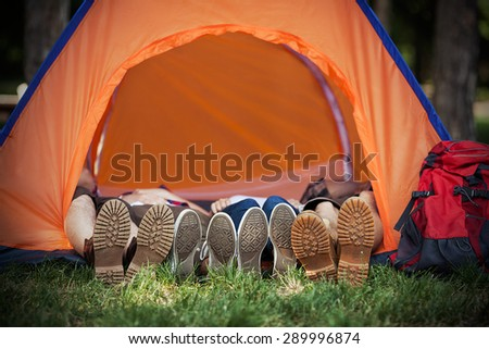 Four hikers wearing hiking boots and sneakers lying down inside a dome tent - stock photo