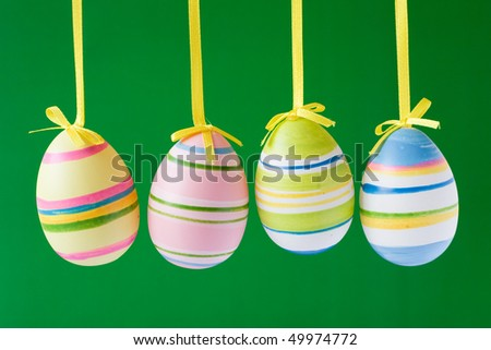 four hung easter eggs isolated on green background