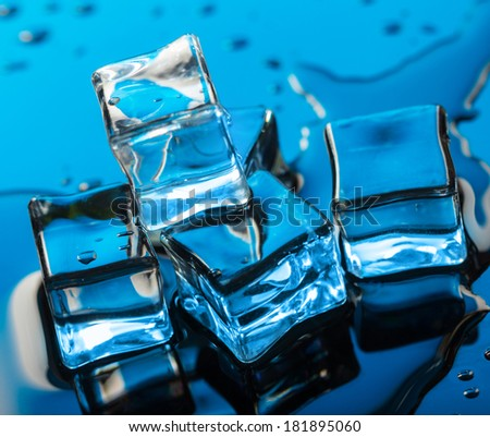 Four ice cube with water drop over blue background.