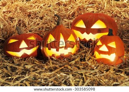 four illuminated halloween pumpkins on straw in red sunset light - stock photo