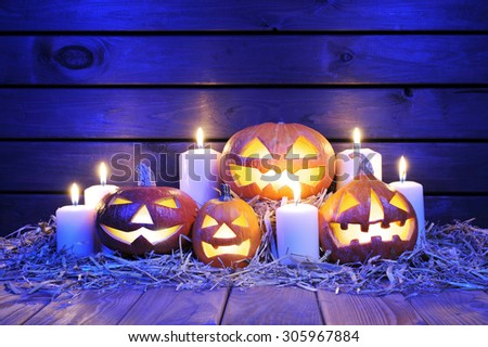 four illuminated halloween pumpkins with candles on straw in front of old weathered wooden board in blue sunset light - stock photo