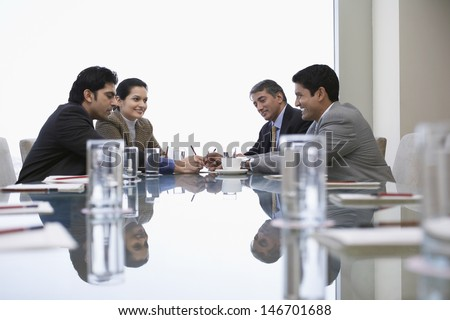 Four Indian business people discussing at conference table - stock photo
