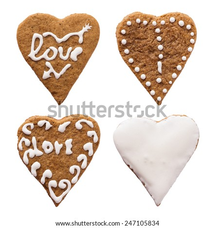Four individual heart-shaped cookies for Valentines Day over white - stock photo