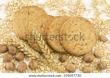 Four integral cookies with hazelnuts and wheat plant on white background