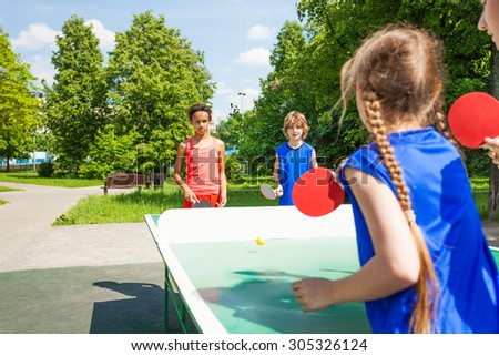 Four international friends play table tennis - stock photo