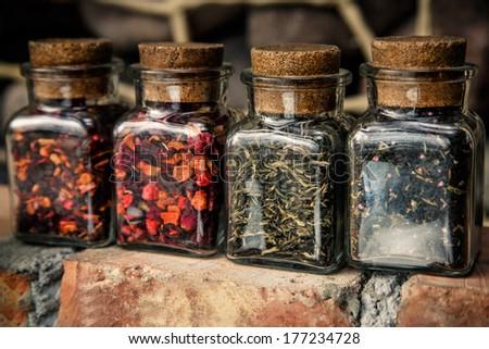 Four jars of loose tea leaves on a brick wall - stock photo