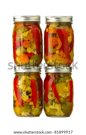 Four jars of pickled vegetables isolated