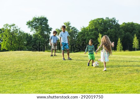 Four kids are playing with a ball on evening glade. - stock photo