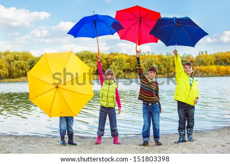 Four kids  in autumn clothing with umbrellas - stock photo
