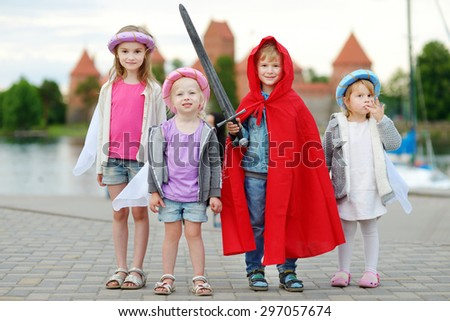 Four kids in princesses and a knight costumes having fun outdoors - stock photo