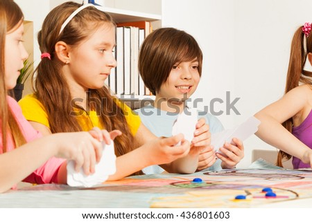 Four kids playing cards for a pastime