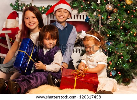 Four kids sitting side by side to fireplace with presents and Christmas tree - stock photo