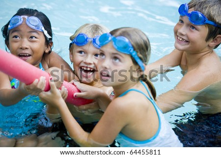 Four kids (7 to 9 years) playing tug of war with pool toy, girl in foreground not in focus - stock photo