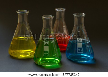 Four laboratory flasks with colorful liquids isolated on dark background.