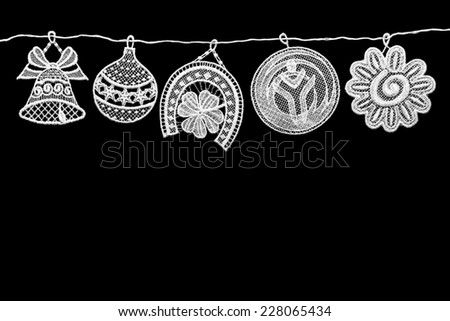 Four lace Christmas decoration on a rope. Isolated on a black background. - stock photo