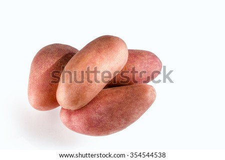Four large red potatoes are heaped against a white background - stock photo