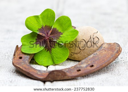 four leaf clover, horseshoe with stone and writing on wood, 2015 - stock photo