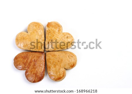 Four-leaf clover of gingerbread composed of four gingerbread hearts on white background - stock photo