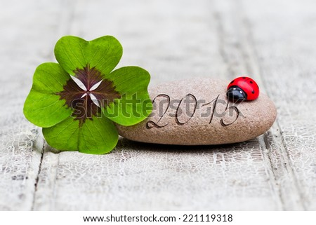four leaf clover with stone and ladybug on wood, 2015 - stock photo
