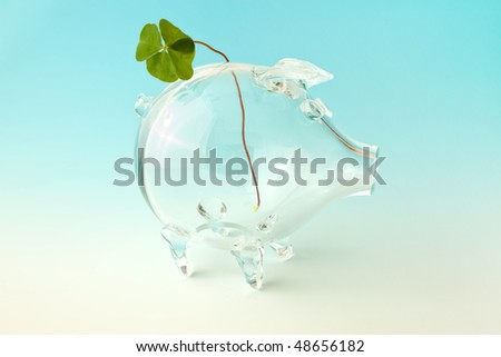 Four-leafed clover in an empty glass piggybank