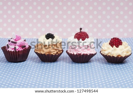 four little baby cupcakes in a row - stock photo