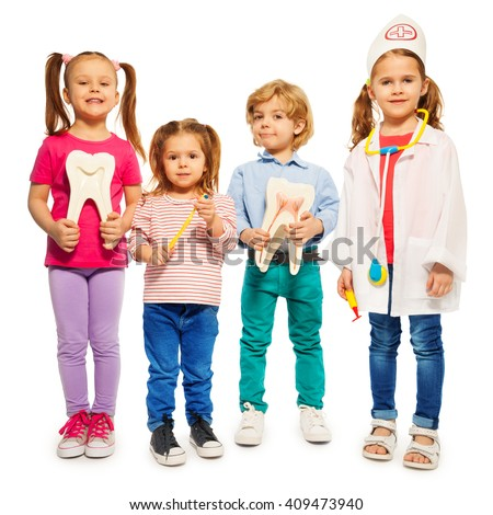 Four little children playing doctors with teeth dummies, toothbrush and stethoscope, isolated on white background - stock photo