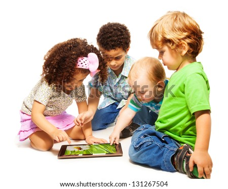 Four little kids playing with tablet computer, isolated on white - stock photo
