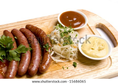 Four long frankfurters with sauerkraut,  herbs and two kinds of sauces - mustard and ketchup on wooden board - stock photo