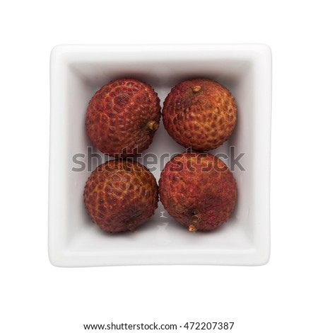 Four lychees in a square bowl isolated on white background
