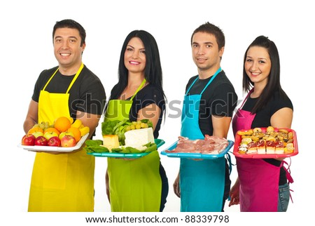 Four market workers standing in a line and holding their fresh products on plateau isolated on white background