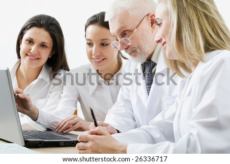 Four medicine workers discuss computer work - stock photo