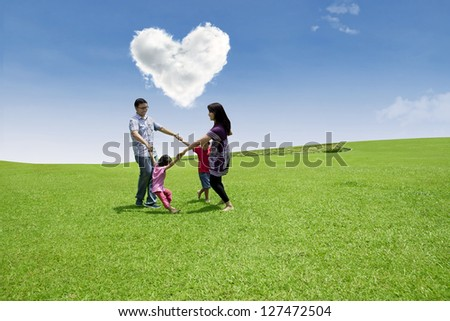 Four member of family dancing under the love sky on green field