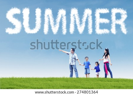 Four member of happy asian family looking at something on the meadow under a summer's cloud - stock photo