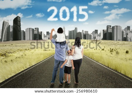 Four member of happy family walking on the highway toward the city to get better future with numbers 2015 on the sky - stock photo