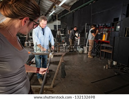 Four men and women busy in a glass making workshop - stock photo